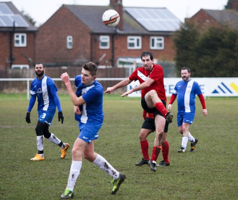 A Charlton player athletically clears the ball while 16-year-old debutant Josh Burrows takes evasive action